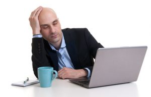 Tired businessman sleeping on a laptop