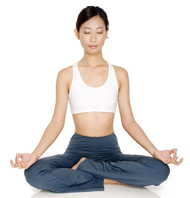 A young asian woman relaxes with her eyes closed in a yoga pose